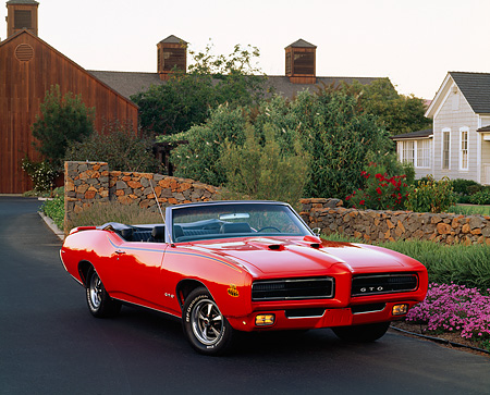AUT 22 RK0478 05 © Kimball Stock 1969 Pontiac GTO The Judge Convertible Red 3/4 Front View On Pavement By Homes Flowers And Trees