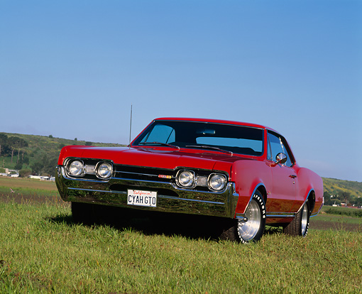AUT 22 RK0488 04 © Kimball Stock 1967 Oldsmobile Cutlass 442 Red 3/4 Front View On Grass