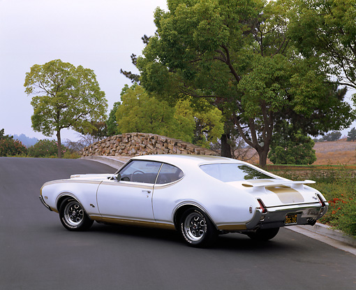 AUT 22 RK0956 02 © Kimball Stock 1969 Oldsmobile Hurst/Olds 455 White And Gold 3/4 Rear View On Pavement By Trees