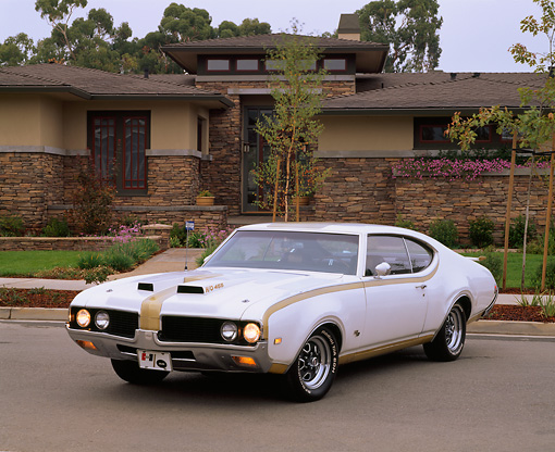 AUT 22 RK0961 02 © Kimball Stock 1969 Hurst Oldsmobile 455 White And Gold 3/4 Front View On Pavement By House