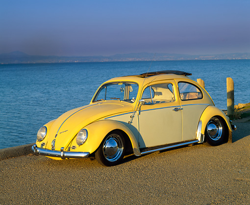 AUT 22 RK1056 01 © Kimball Stock 1960 VW Beetle With Sunroof Yellow 3/4 Front View On Pavement By Water