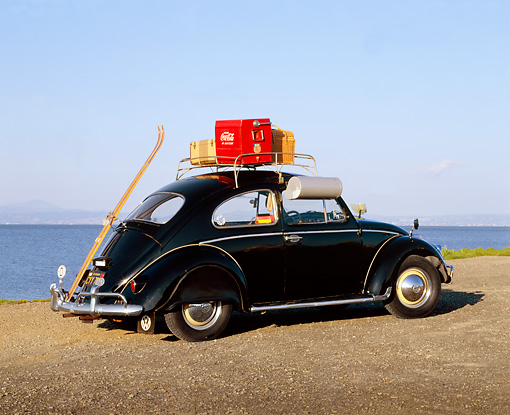 AUT 22 RK1063 04 © Kimball Stock 1960 Volkswagen Beetle Black With Roof Rack 3/4 Rear View On Pavement By Water Blue Sky
