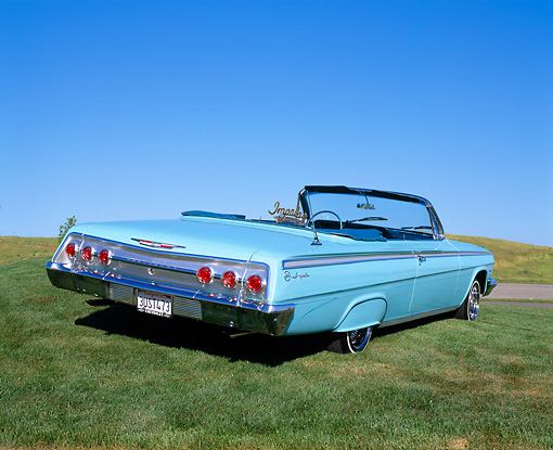 AUT 22 RK1080 02 © Kimball Stock 1962 Chevy Impala Light Blue 3/4 Rear View On Grass Blue Sky