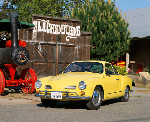 AUT 22 RK1103 02 © Kimball Stock 1969 VW Karmann Ghia Yellow Front 3/4 View On Pavement By Barn And Train