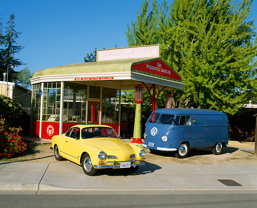 AUT 22 RK1104 10 © Kimball Stock 1969 Volkswagen Karmann Ghia Yellow And 1955 Volkswagen Barn Door Panel Bus Blue By Old Gas Station