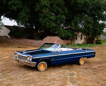 AUT 22 RK1123 02 © Kimball Stock 1964 Chevy Impala SS Convertible Lowrider Blue Side 3/4 View On Dirt By Tree