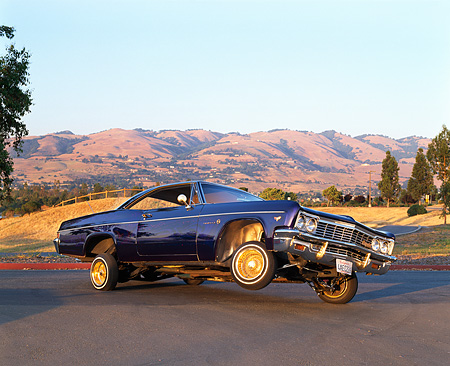 AUT 22 RK1139 02 © Kimball Stock 1966 Chevy Impala Lowrider Purple 3/4 Side View On Pavement Mountains Blue Sky