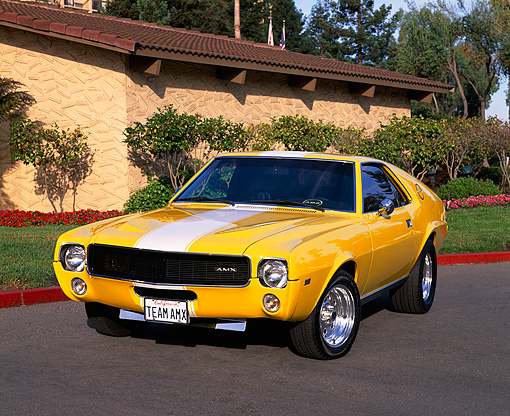 AUT 22 RK1175 01 © Kimball Stock 1968 AMC AMX Yellow With White Stripe 3/4 Front View On Pavement By Building