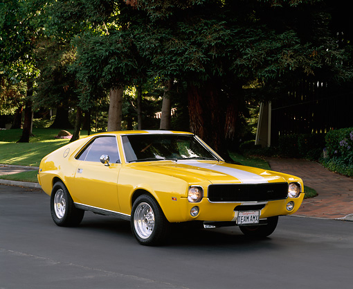 AUT 22 RK1177 03 © Kimball Stock 1968 AMC AMX Yellow With White Stripe 3/4 Front View On Pavement By Trees