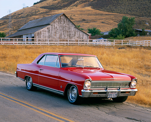 AUT 22 RK1183 05 © Kimball Stock 1966 Chevy Nova SS Red 3/4 Front View On Road By Dry Grass And Barn