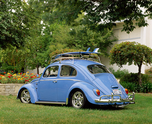 AUT 22 RK1206 04 © Kimball Stock 1964 Volkswagen Beetle Light Blue With Surfboard 3/4 Rear View On Grass By Flowers And Trees