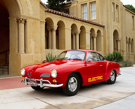AUT 22 RK1248 06 © Kimball Stock 1968 VW Karmann Ghia Electric Car Red 3/4 Front View On Pavement By Building