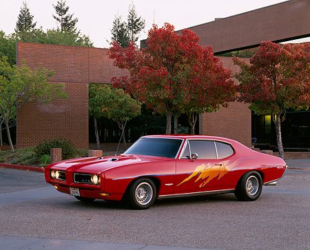 AUT 22 RK1274 02 © Kimball Stock 1968 Pontiac GTO Red Custom Design 3/4 Side View On Pavement By Building And Fall Trees