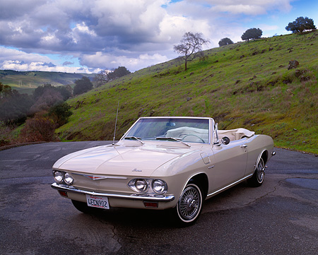AUT 22 RK1302 11 © Kimball Stock 1965 Chevrolet Corvair Corsa Convertible Beige 3/4 Front View On Pavement Grass Hills Background
