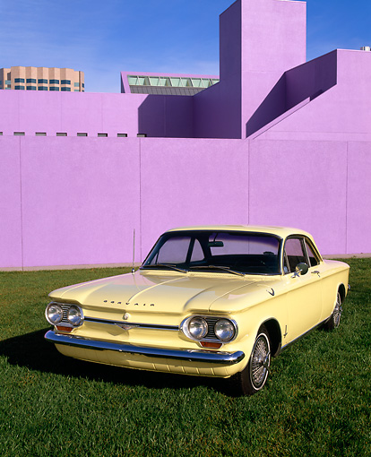 AUT 22 RK1349 05 © Kimball Stock 1964 Chevrolet Corvair Monza Sport Yellow 3/4 Front View On Grass By Purple Building