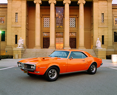 AUT 22 RK1405 01 © Kimball Stock 1968 Pontiac Firebird Orange 3/4 Front View On Pavement By Building
