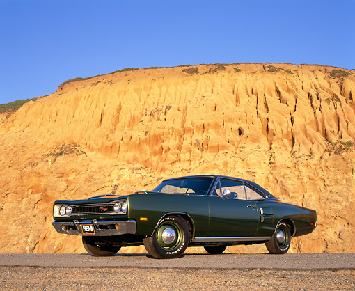 AUT 22 RK1498 02 © Kimball Stock 1969 Dodge Hemi Coronet RT Green Low 3/4 Side View On Pavement Against Rock