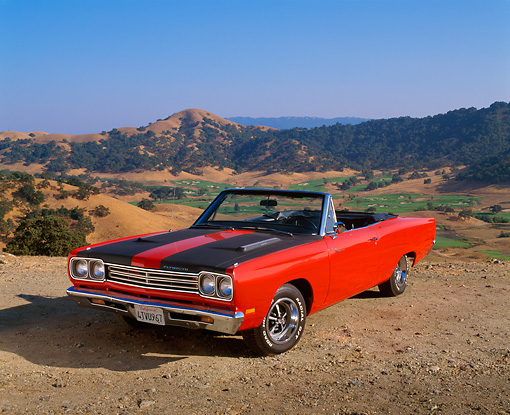 AUT 22 RK1535 01 © Kimball Stock 1969 Plymouth Road Runner Convertible Red With Black Stripes 3/4 Front View On Dirt Hills Background
