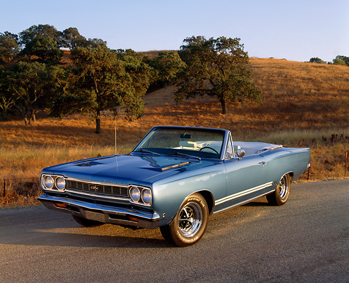 AUT 22 RK1537 06 © Kimball Stock 1968 Plymouth GTX 440 Convertible Blue 3/4 Front View On Pavement By Trees