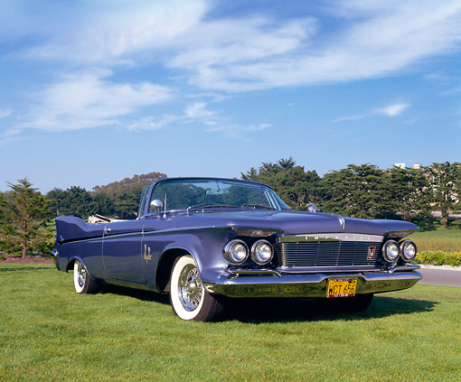 AUT 22 RK1556 03 © Kimball Stock 1961 Imperial Crown Convertible Blue Low 3/4 Front View On Grass Blue Sky