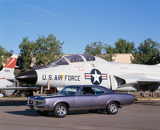 AUT 22 RK1614 03 © Kimball Stock 1967 Pontiac GTO Metallic Blue 3/4 Side View On Pavement By Military Airplane