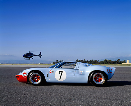 AUT 22 RK1718 03 © Kimball Stock 1968 Ford GT40 Light Blue And Orange FAV Car Profile On Pavement With Helicopter Blue Sky