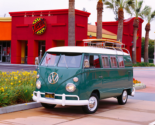 AUT 22 RK1791 02 © Kimball Stock 1967 Volkswagen Bus Teal And White With A Surfboard 3/4 Front View By Palm Trees And Building