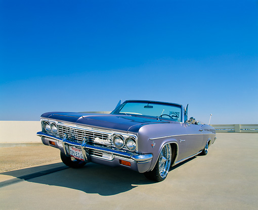 AUT 22 RK1808 02 © Kimball Stock 1966 Chevy Impala Convertible Violet 3/4 Front View Raised On Pavement Blue Sky