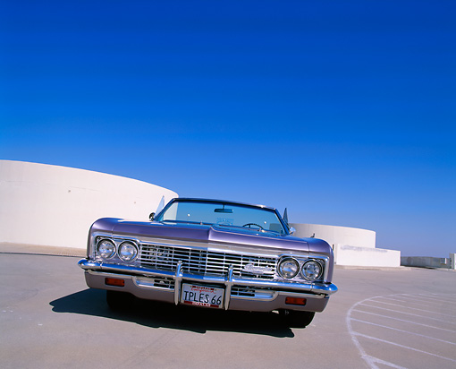 AUT 22 RK1811 01 © Kimball Stock 1966 Chevrolet Impala Convertible Violet Low Slanted Head On Shot On Pavement Blue Sky