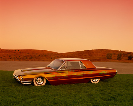 AUT 22 RK1831 06 © Kimball Stock 1964 Ford Thunderbird With Flames Lowrider 3/4 Front View On Grass By Hills
