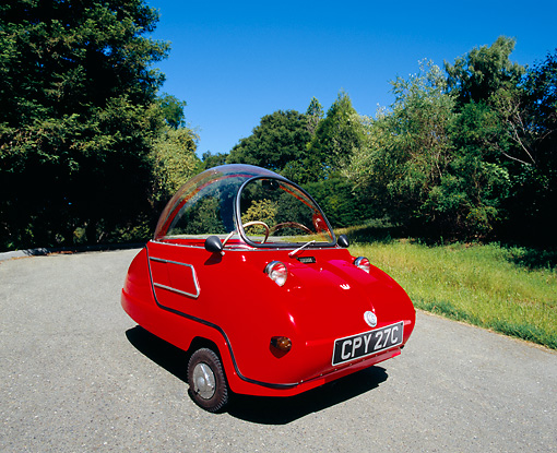 AUT 22 RK1938 03 © Kimball Stock 1964 Peel Trident Microcar Red 3/4 Front View On Pavement By Trees