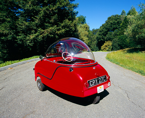 AUT 22 RK1940 01 © Kimball Stock 1964 Peel Trident Microcar Red 3/4 Rear View On Pavement By Trees