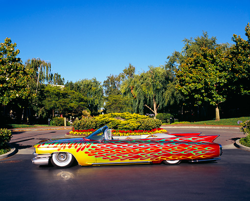 AUT 22 RK1954 01 © Kimball Stock 1960 Cadillac Convertible Custom Flames Profile View On Pavement By Trees And Flowers