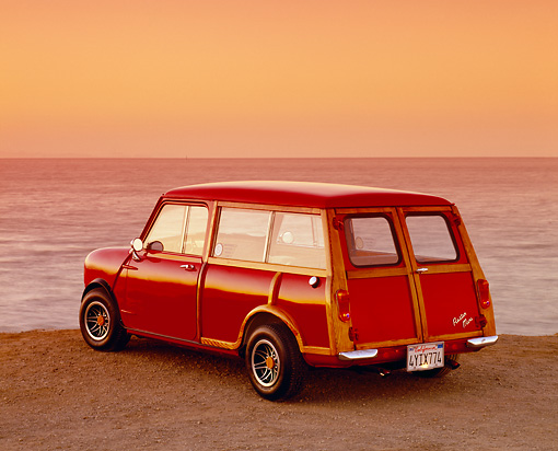 AUT 22 RK2006 01 © Kimball Stock 1962 Austin Mini Traveller Woody Red With White Stripes 3/4 Rear View On Sand By Ocean