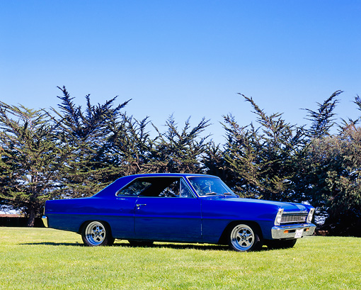 AUT 22 RK2026 02 © Kimball Stock 1966 Chevy Nova SS Blue 3/4 Side View On Grass Trees Background Blue Sky