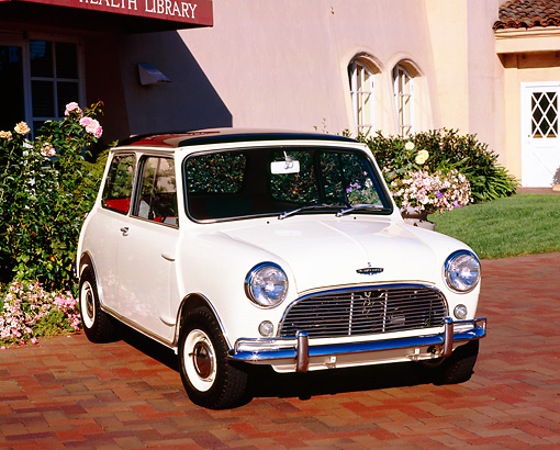 AUT 22 RK2052 01 © Kimball Stock 1966 Austin Mini Cooper S White Black Top 3/4 Front View On Brick Pavement By Building