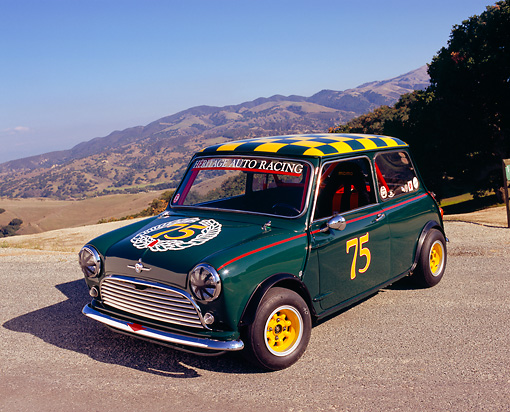 AUT 22 RK2104 01 © Kimball Stock 1964 Morris Mini Cooper Green And Yellow 3/4 Front View On Pavement Mountains Background