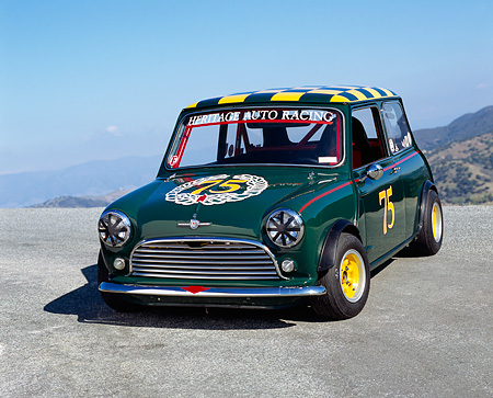 AUT 22 RK2107 04 © Kimball Stock 1964 Morris Mini Cooper Green And Yellow 3/4 Front View On Pavement Hill Blue Sky