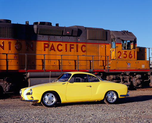 AUT 22 RK2124 02 © Kimball Stock 1961 VW Karmann Ghia Yellow White Stripe 3/4 Side View On Gravel By Train