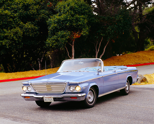 AUT 22 RK2223 01 © Kimball Stock 1964 Chrysler Newport Convertible Blue 3/4 Front View On Pavement By Trees