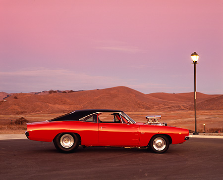 AUT 22 RK2299 02 © Kimball Stock 1968 Dodge Charger R/T 528  Hemi Orange Low Profile On Pavement By Lake And Snowy Mountains