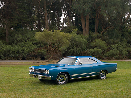 AUT 22 RK2415 01 © Kimball Stock 1968 Plymouth GTX Blue 3/4 Side View On Grass Trees Background