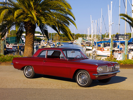 AUT 22 RK2523 01 © Kimball Stock 1962 Pontiac Tempest LeMans Burgundy 3/4 Side View On Pavement By Harbor