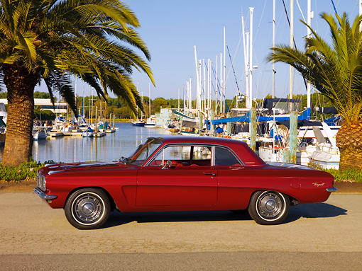 AUT 22 RK2524 01 © Kimball Stock 1962 Pontiac Tempest LeMans Burgundy 3/4 Front View On Pavement By Harbor