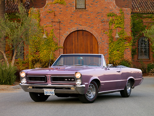 AUT 22 RK2615 01 © Kimball Stock 1965 Pontiac GTO Convertible Lavender Front 3/4 View On Pavement By Building Tree Ivy