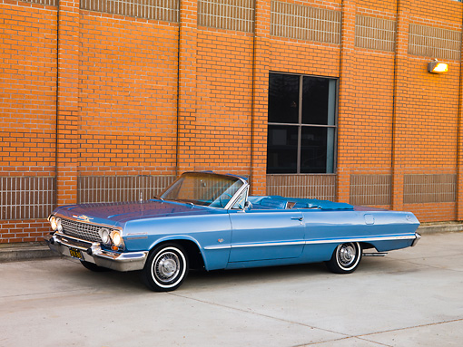 AUT 22 RK2716 01 © Kimball Stock 1963 Chevrolet Impala Convertible Blue 3/4 Front View On Pavement By Building