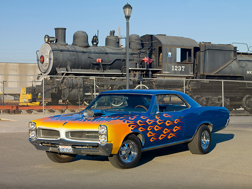 AUT 22 RK2732 01 © Kimball Stock 1966 Pontiac LeMans Blue Orange Flames 3/4 Front View On Pavement By Train