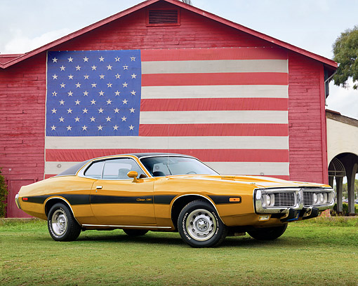 AUT 23 BK0011 01 © Kimball Stock 1973 Dodge Charger SE 440 Yellow 3/4 Side View On Grass By American Flag On Barn