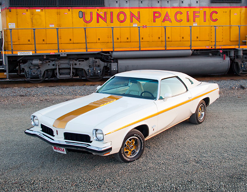 AUT 23 BK0039 01 © Kimball Stock 1973 Oldsmobile Cutlass White And Gold Stripe 3/4 Front View On Gravel By Train