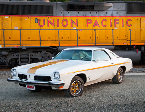 AUT 23 BK0041 01 © Kimball Stock 1973 Oldsmobile Cutlass White And Gold Stripe 3/4 Front View On Gravel By Train